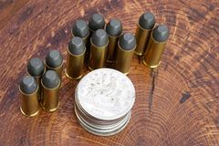 Revolver cartridges and Silver Dollar Wild West period on wooden background. The .45 Revolver cartridges and Silver Dollar Wild West period on wooden background Stock Photo