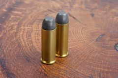 The .45 Revolver cartridges Wild West period. On wooden background Stock Photography