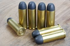 The .45 Revolver cartridges Wild West period. On wooden background Stock Photos