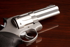 Revolver Close Up. Close-up shot of .357 revolver on reflective wooden surface Royalty Free Stock Photos