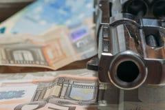 Revolver, der auf einem Stapel des Geldes liegt stockfotografie