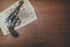 Revolver en geld op de lijst Royalty-vrije Stock Afbeeldingen