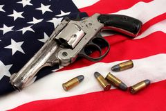 Revolver on a Flag. Old revolver and 4 bullets on an American flag Royalty Free Stock Photography