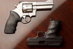 Revolver gegen Pistole Stockbild
