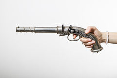 A revolver in girl's hand. Girl's hand with bracelet holds a silver revolver Stock Photography
