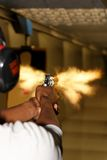 Revolver Gun fired with Muzzle Flash. A picture taken over the shoulder of a young man firing a gun at a shooting range in the precise moment of the muzzle flash Royalty Free Stock Images