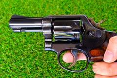 Revolver gun in hand on grass background. Gun background grass with ammunition Royalty Free Stock Photo