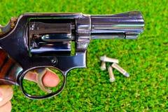 Revolver gun in hand on grass background. Gun background grass with ammunition Stock Photography