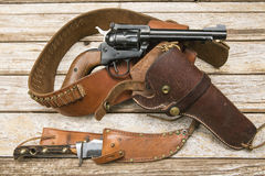 Revolver holster knive wood background. The six shooter pistol with ammo belt and leather holster rests on the cracked and grungy wood plank panel, along with Royalty Free Stock Photography