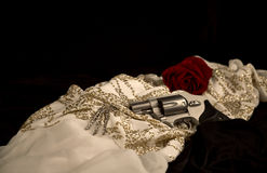 Revolver laying on a Woman's Evening Dress Royalty Free Stock Images