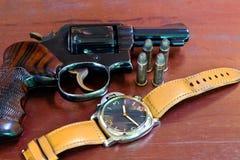Revolver mit Kugeln auf braunen Holztischen und Uhren Lizenzfreies Stockbild