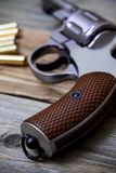 Revolver pistol with ammunition. On an old wooden surface. handle closeup Stock Images