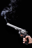 Revolver with smoke. Hand holding a revolver with smoking barrel, against black background Royalty Free Stock Image