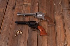 Revolver. Two revolvers with bullets on a wooden background Royalty Free Stock Images