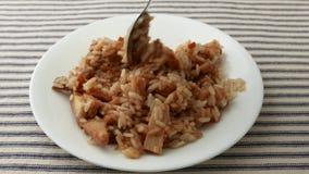 Revolviendo y comiendo un pollo con la cena de TV del arroz almacen de video