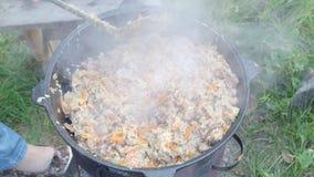 Revolvimiento del plov en el pote de Kazán en el horno al aire libre almacen de video