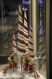 Revolving Christmas Elves with Candy Canes. Christmas elves and conical candy canes on display in a revolving door stock images