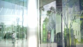 Revolving glass door. People using automatic revolving glass door or entering rotating spinning glass doorway. Entrance to the hotel,business ,exhibition or stock footage