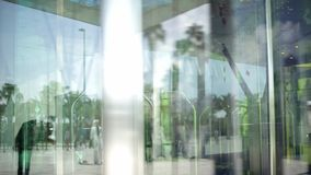 Revolving Glass Door. People using automatic revolving glass door or entering rotating spinning glass doorway. Entrance to the hotel,business ,exhibition or stock video footage