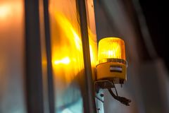 Revolving warning light shining on corrugated metal wall. Close-up detail of a yellow revolving warning light shining onto a metal wall at a construction site Stock Photos