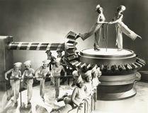 Revuetänzerinnen, die auf Maschinenteil tanzen Stockfotos