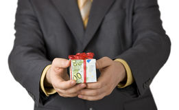 Reward. Man offering an expensive gift box wrapped in euro banknotes Royalty Free Stock Photography