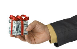 Reward. Man offering an expensive gift box wrapped in us dollar bills Stock Image