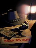 Reward. Announcement on a wooden table, with one hundred dollars bank notes, a gun, a hat, all enlightened by a lamp Stock Photography