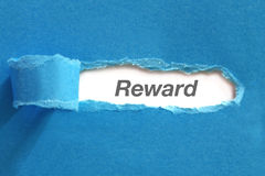 Reward. Text appearing behind blue color paper Royalty Free Stock Photos