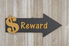 Reward this way sign. Reward text on an arrow chalkboard sign with gold dollar sign on weathered wood Stock Photo