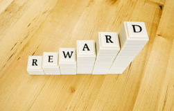 Reward word. A photograph of the word reward, spelt out in block letters, taken on brown wooden background. Concept image for good returns in investments Stock Photos