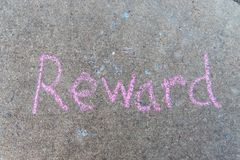 Reward written with pink sidewalk chalk on gray concrete pavement background stock photo