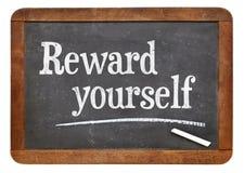 Reward yourself. Motivational words on a vintage slate blackboard Stock Image