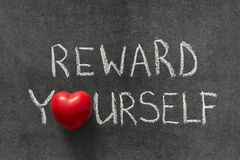 Reward yourself. Phrase handwritten on blackboard with heart symbol instead of O Stock Images