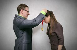 Award ceremony. Awarding a gold medal. Rewarding a person with a gold medal for first place and victory at competitions or business success isolated on gray stock photo