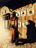 Rewards. Reward announcements on a wooden wall close to the county jail. A bounty hunter is looking at them Stock Photo