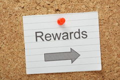 Rewards This Way. The word Rewards with an arrow pointing in the right direction on a paper note pinned to a cork notice board Royalty Free Stock Photos