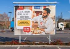 REWE超级市场信息海报在停车场站立 免版税库存图片