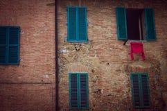 Rewolucjonistka długiego rękawa koszulowa osuszka w słońcu przed typowym budynkiem w Tuscany obrazy royalty free