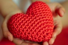 Rewolucjonistka dziający serce wewnątrz w dziecka ` s rękach Fotografia Stock
