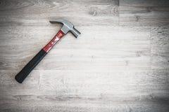 Rewolucjonistka młot na drewnianej podłoga, wewnętrznym budowy narzędziu lub domowym naprawiania odświeżania pojęciu, ciemny brzm Obrazy Stock
