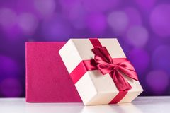 Rewolucjonistka prezenta otwarty pudełko z łękiem na białym biurka i purpur bokeh zdjęcie royalty free