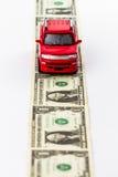 Rewolucjonistka zabawkarski samochód na pieniądze drodze. Obrazy Stock