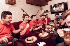Rewolucjonistki drużyny fan rozweselają podczas gdy błękit drużyny fan są smutni Siedzą przy sporta barem fotografia royalty free