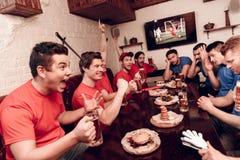 Rewolucjonistki drużyny fan rozweselają podczas gdy błękit drużyny fan są smutni Siedzą przy sporta barem obrazy royalty free