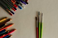 Rewolucjonistki i zieleni ciency paintbrushes i stubarwni ołówki na białego papieru tle jako rysunkowy pojęcie Zdjęcia Royalty Free