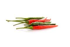 Rewolucjonistki i zieleni gorącego chili pieprze z trzonem na bielu Zdjęcie Royalty Free
