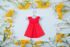 Rewolucjonistki origami papierowa suknia na wieszaku otaczającym z żółtymi i białymi małymi kwiatami na światło mennicy tle Obraz Stock