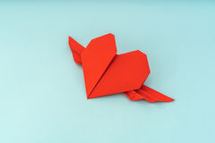 Rewolucjonistki origami papierowy serce z skrzydłami na błękitnym tle Obrazy Stock