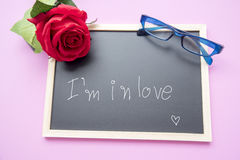 Rewolucjonistki róża, błękitni szkła i blackboard na różowym blackboard, Fotografia Stock